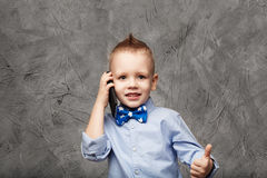 Portrait of a cute little boy in blue shirt and bow tie with mob Royalty Free Stock Photos