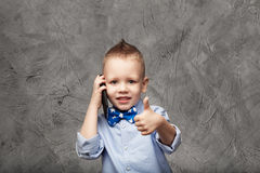 Portrait of a cute little boy in blue shirt and bow tie with mob Stock Photography