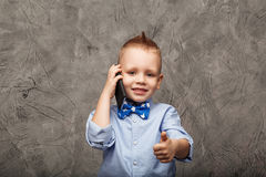 Portrait of a cute little boy in blue shirt and bow tie with mob Royalty Free Stock Photography