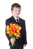Portrait of cute little boy in business suit giving flowers to s Royalty Free Stock Photos