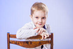 Portrait of cute little boy on chair Stock Photo