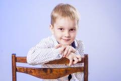 Portrait of cute little boy on chair Stock Photo