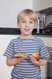 Portrait of cute little boy choosing between apple and chocolate chip cookie Stock Image
