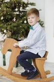 Portrait of a cute little boy. Little boy among Christmas decorations. Boy riding a rocking deer. Rocking deer chair for kids. Ride playing stock photo