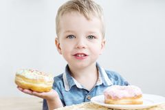Portrait of a cute little boy eating donuts stock photo