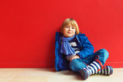Portrait of a cute little boy. Fashion portrait of adorable little boy of 4-5 years old, wearing blue jacket, scarf and stripes rain boots, sitting on the floor Stock Images