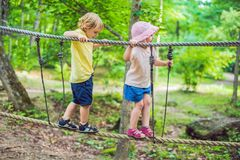 Portrait of cute little boy and girl walk on a rope bridge in an. Adventure rope park stock photo