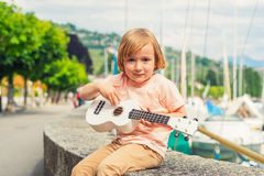 Portrait of a cute little boy. Little happy boy plays his guitar or ukulele Stock Image