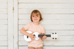 Portrait of a cute little boy. Little happy boy plays his guitar or ukulele Stock Photography