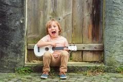 Portrait of a cute little boy. Little happy boy plays his guitar or ukulele Royalty Free Stock Photos