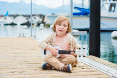 Portrait of a cute little boy. Little happy boy plays his guitar or ukulele, resting by the lake Royalty Free Stock Photography
