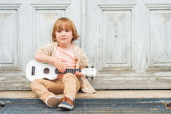 Portrait of a cute little boy. Little happy boy plays his guitar or ukulele, sitting by the wooden door outdoors Royalty Free Stock Photos