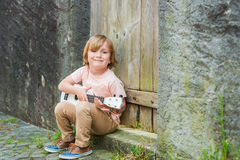 Portrait of a cute little boy. Little happy boy plays his guitar or ukulele, sitting by the wooden door outdoors Stock Photos