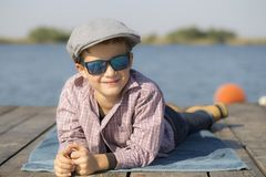 Portrait of a cute little boy with a hat and sunglasses, sitting. By the river - the lake and enjoy the beautiful and sunny day Royalty Free Stock Photo