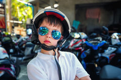 Portrait of cute little boy in helmet and sunglasses before riding a motorcycle Stock Images