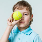 Portrait of a cute little boy holding a tennis ball at the eye Stock Photos
