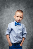 Portrait of a cute little boy in jeans, blue shirt and bow tie Royalty Free Stock Image