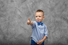 Portrait of a cute little boy in jeans, blue shirt and bow tie o Royalty Free Stock Image