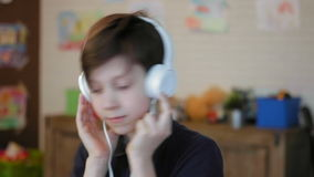Portrait of a cute little boy listening to the music wearing headphones stock footage