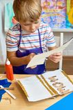 Little Boy Making Handmade Card for Mom. Portrait of cute little boy making  handmade gift card for mom during art and craft class in pre-school Stock Image