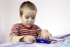 Portrait of cute little boy with markers in bed stock images