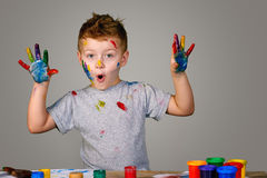 Portrait of a cute little boy messily playing with paints Royalty Free Stock Photos