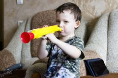 Portrait of cute little boy playing flute in toy stock image
