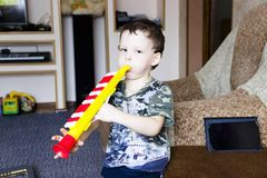 Portrait of cute little boy playing flute in toy royalty free stock photo