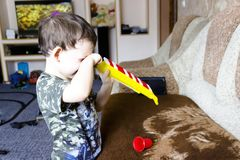 Portrait of cute little boy playing flute in toy stock images