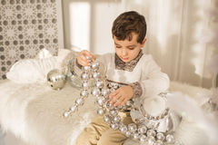 Portrait of cute little boy plays with a big glass toy on a bed Royalty Free Stock Image