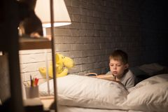 Cute Little Boy Reading in Bed royalty free stock photo
