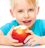 Portrait of a cute little boy with red apple Stock Image
