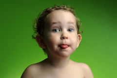 Portrait of cute little boy showing his tongue. Close up portrait of cute little boy showing his tongue on green background Stock Images