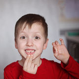 Portrait cute  little Boy shows the First dropped-out milk Tooth Stock Image