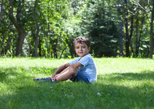 Portrait of cute little boy sitting on the grass Royalty Free Stock Photo