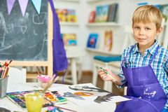 Nice Little Boy in Art Studio. Portrait of cute little boy smiling at camera while painting Halloween picture sitting at table in art class, copy space stock image