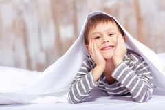 Portrait of a cute little boy under the blanket Royalty Free Stock Photography