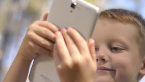 Portrait Of Cute Little Boy Using Digital Tablet Outdoor. Portrait Of Cute Little Boy Playing With A Tablet Outdoor,Summertime stock footage