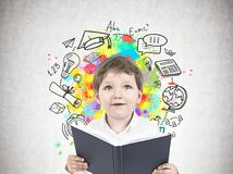 Cute little boy with a book, school. Portrait of a cute little boy in a white shirt holding an open book and looking upwards. A concrete wall with an education Stock Photography