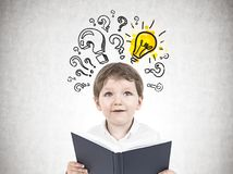 Cute little boy with a book, questions and answer. Portrait of a cute little boy in a white shirt holding an open book and looking upwards. Question marks and a Stock Image