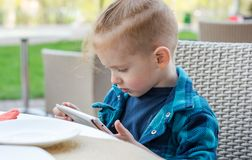 Portrait of a cute little boy who playing on a tablet in a cafe. Portrait of a cute little boy who playing on a tablet in a street cafe royalty free stock photos