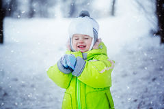 Portrait of cute little boy in winter clothes with falling snow. Kid playing and smiling in nature cold day Royalty Free Stock Photography