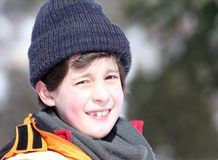 Portrait of a cute little boy with wool cap and winter jacket. In the mountains royalty free stock image