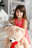 Portrait of a cute little brunette girl hugging a soft teddy bea Royalty Free Stock Photography