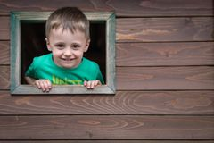 Boy looking through the window. Portrait of a cute little Caucasian boy looking through the window of a wooden toy house in a outdoor playground stock photo