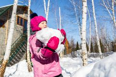 Portrait of cute little caucasian girl in sport winter jacket abearing big snowball and having fun playing outdoors with snow. Winter vacation and holidays stock photography