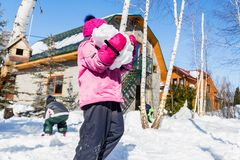 Portrait of cute little caucasian girl in sport winter jacket abearing big snowball and having fun playing outdoors with snow. Winter vacation and holidays royalty free stock images