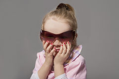 Portrait of Cute Little Caucasian Girl In Sunglasses. Against Gr Stock Image