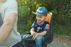 Portrait of Cute little caucasian 3 years old toddler baby boy child wearing cap in the seat bicycle behind father, outdoors stock photography