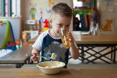 Portrait of Cute little caucasian 3 years old toddler boy child drinking fruit juice in a glass, Smiling boy sitting at restaurant. Cafe, hotel holding glass of Royalty Free Stock Photo
